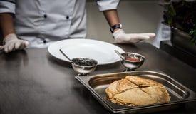 Crêpes et deux genres de caviar dans des plats en métal sur une profession photographie stock libre de droits