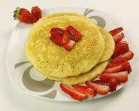 Crêpes et fraises sur le fond blanc Images stock