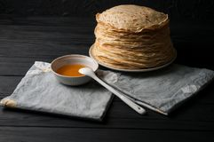 Crêpes faites maison avec du miel et des noix, plat blanc de vintage, plongeur, table en bois foncée Images stock