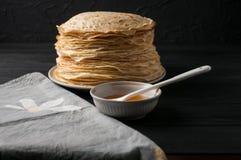 Crêpes faites maison avec du miel et des noix, plat blanc de vintage, plongeur, table en bois foncée Photos libres de droits