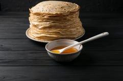 Crêpes faites maison avec du miel et des noix, plat blanc de vintage, plongeur, table en bois foncée Photos stock