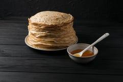 Crêpes faites maison avec du miel et des noix, plat blanc de vintage, plongeur, table en bois foncée Images libres de droits
