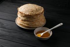 Crêpes faites maison avec du miel et des noix, plat blanc de vintage, plongeur, table en bois foncée Image libre de droits
