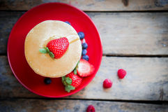 Crêpes faites maison savoureuses avec des fraises, des myrtilles et l'érable Photographie stock libre de droits