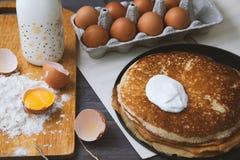 Crêpes fraîches et chaudes dans une poêle, oeufs, lait, farine sur une table en bois Vue supérieure image libre de droits