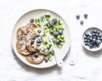Crêpes libres de gluten avec du yaourt, le kiwi et les myrtilles de noix de coco sur un fond clair photo stock