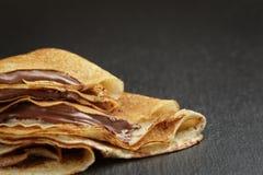 Crêpes ou blinis minces avec de la crème de chocolat dessus Photos libres de droits