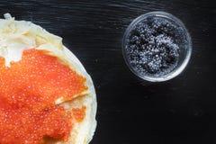Crêpes russes minces traditionnelles avec le caviar rouge sur un fond en bois rustique foncé images stock