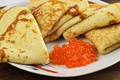Crêpes russes traditionnelles avec le caviar rouge images stock