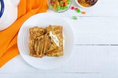 Cr?pes sensibles d?licieuses avec le fromage blanc et les raisins secs sur un fond en bois blanc D?jeuner sain image libre de droits