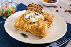 Crêpes sensibles délicieuses avec le fromage blanc, la vanille et les raisins secs d'un plat images libres de droits