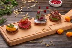Crêpes sur un fond en bois Foyer sélectif crêpes avec le caviar de brochet, le pâté de canard, les poissons, la viande et le pros photographie stock libre de droits