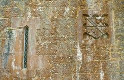 Crête et fenêtre dans le mur moussu de château Image stock