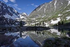 Crêtes couronnées de neige et lac de montagne de la chaîne de Sikhote-Alin Sikhote Alin, un pays montagneux en Extrême Orient image stock