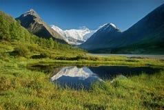 Crêtes couronnées de neige et lac de montagne Réflexion des montagnes couronnées de neige dans l'eau de lac Horizontal de montagn images libres de droits