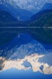 Crêtes de montagne se reflétant dans le lac Image libre de droits