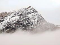 Crêtes neigeuses pointues des montagnes d'Alpes au-dessus de vallée complètement de brouillard gris lourd Photos stock