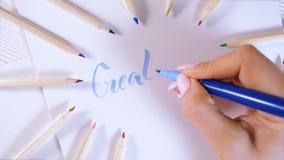 críe A mão fêmea escreve letras azuis bonitas na lona no quadro colorido das penas Roteiro da caligrafia Arte da escrita video estoque
