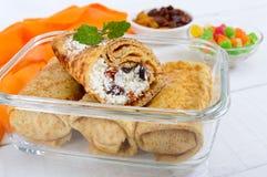 Cr?pes sensibles d?licieuses avec le fromage blanc et les raisins secs dans un conteneur en verre sur un fond en bois blanc photo libre de droits