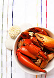 Crab. A bowl of freshly steamed crab claws, presented in a white bowl, placed on a thin-striped tea cloth with pebbles and coral to suggest freshness of the Royalty Free Stock Image