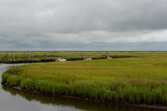 Crab Boats Sitting Quietly in the Wetlands. Three empty crab boats are quietly idle in the water of the wetlands with cloudy skies in the background Stock Image