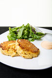 Crab Cakes and Greens. Fresh crab cakes on a white plate with sauce and a salad of field greens royalty free stock images