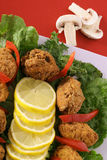 Crab cakes and lemon slices stock photography