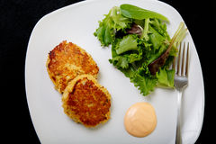 Crab Cakes and Salad on Black From Above Royalty Free Stock Photos