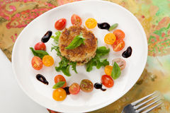 Crab Cakes and Tomato Salad Stock Photos