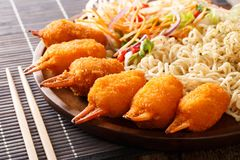 Crab claws breaded served with udon noodles and fresh vegetable. Salad close-up on a plate on the table. horizontal stock image