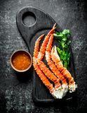 Crab on a cutting Board with greens and sauce in a bowl. On dark rustic background stock photo