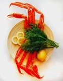 Crab garras em uma placa, em um limão e em uns verdes de madeira no backgrou branco Foto de Stock