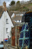 Crab Pots at Cadgwith Cove Cornwall. Crab and lobster pots await their next use in the spring sunshine among the thatched cottages of Cadgwith Cove in Cornwall Royalty Free Stock Photo