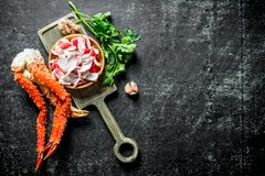 Crab meat and fresh crab on a cutting Board with greens and garlic. On dark rustic background stock photo