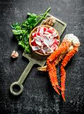 Crab meat and fresh crab on a cutting Board with greens and garlic. On dark rustic background royalty free stock images