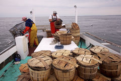 Crab pots and fishermen on a fishing boat Stock Photography