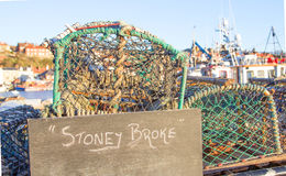 Crab pots with stoney broke sign in front of harbour Royalty Free Stock Image