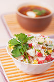 Crab salad and Russian borscht. Crab salad with mayonnaise and Russian borscht to striped fabric stands on light table Stock Image