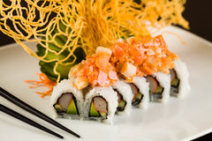 Crab and Salmon Roll. Fancy crab and salmon roll with avocado on a white plate garnished with sliced cucumber and crispy noodles Royalty Free Stock Image
