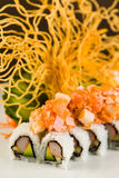 Crab and Salmon Roll. Fancy crab and salmon roll with avocado on a white plate garnished with sliced cucumber and crispy noodles Royalty Free Stock Photos