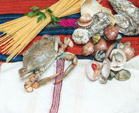 Crab , seafood with spaghetti and shells on ethnic fabric. Stock Images