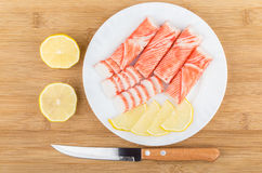 Crab sticks, knife and pieces of lemon in white plate Stock Photography