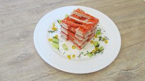 Crab sticks on a white plate with the  Desk stock photography