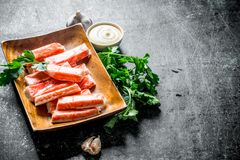 Crab sticks on a wooden plate with greens and sauce. On dark rustic background royalty free stock photo