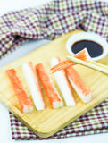 Crab sticks in wooden plate and table cloth Royalty Free Stock Photos