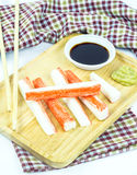 Crab sticks in wooden plate and table cloth on white background Royalty Free Stock Photo