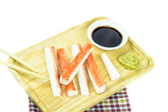 Crab sticks in wooden plate and table cloth on white background Stock Photography