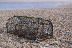 Crabbing pot on warm stony beach. Fishing tackle left to dry on Aldeburgh beach, on the Suffolk coast Royalty Free Stock Image