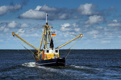 Crabs or shrimp fishing boat on the North Sea under a blue sky w Royalty Free Stock Images