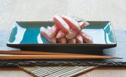 Crabsticks crus frais de sushi de plat avec des baguettes Image libre de droits